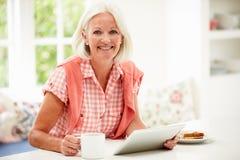 Mulher envelhecida meio que usa a tabuleta de Digitas sobre o café da manhã Fotografia de Stock Royalty Free