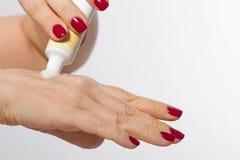 A mulher envelhecida meio 40s lubrifica a pele das mãos com o creme cosmético isolado no branco Zombe acima e copie o espaço, foc Imagens de Stock