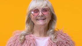 Mulher envelhecida moderna na câmera de sorriso dos vidros cor-de-rosa no fundo amarelo, encanto filme