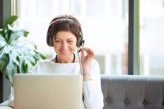Mulher envelhecida nos auriculares e no portátil na tabela fotografia de stock