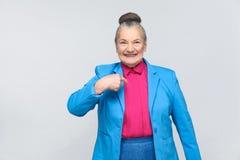 Mulher envelhecida que aponta o dedo ela mesma e sorriso toothy imagem de stock