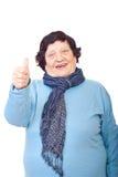 Mulher envelhecida que dá os polegares fotografia de stock