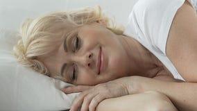 Mulher envelhecida que encontra-se na cama com a cabeça que descansa no descanso, sorrindo, sono confortável filme