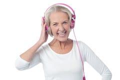 Mulher envelhecida que escuta a música Imagem de Stock Royalty Free