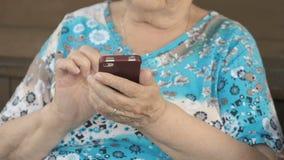 Mulher envelhecida que guarda um smartphone vídeos de arquivo