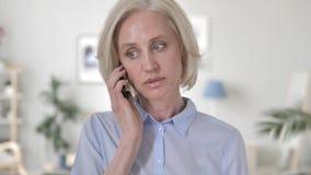 Mulher envelhecida que negocia no telefone video estoque