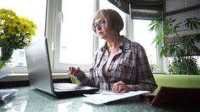 A mulher envelhecida que usa Internet banking na casa vídeos de arquivo