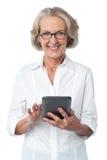 Mulher envelhecida que usa o dispositivo de almofada do toque Fotografia de Stock