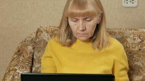 A mulher envelhecida trabalha com cuidado em um portátil em casa no sofá Está datilografando no teclado e está olhando a tela E filme