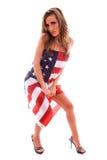 Mulher envolvida na bandeira dos EUA. Imagens de Stock