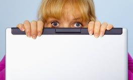 A mulher era culpada e esconde atrás de um computador Fotografia de Stock