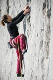 A mulher escala uma rocha Fotos de Stock Royalty Free