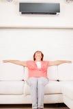 A mulher escapa do calor sob o condicionador de ar Fotografia de Stock Royalty Free