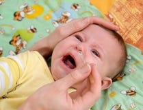 A mulher escava nas gotas em um nariz ao bebê de grito doente Imagem de Stock Royalty Free
