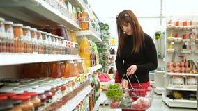 A mulher escolhe as bebidas no supermercado video estoque