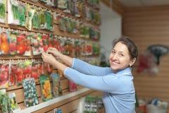 A mulher escolhe as sementes na loja Fotos de Stock Royalty Free