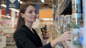 A mulher escolhe azeitonas enlatadas a mercearia, comprando no supermercado do alimento Fotos de Stock