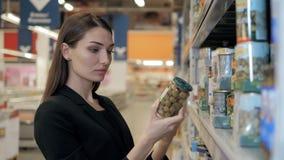 A mulher escolhe azeitonas enlatadas a mercearia, comprando no supermercado do alimento Fotografia de Stock