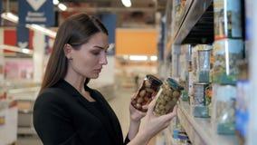 A mulher escolhe azeitonas enlatadas a mercearia, comprando no supermercado do alimento Imagem de Stock