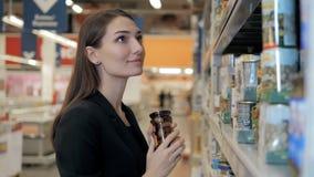 A mulher escolhe azeitonas enlatadas a mercearia, comprando no supermercado do alimento Imagem de Stock Royalty Free