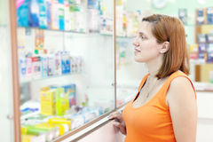 A mulher escolhe drogas na farmácia fotografia de stock