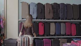 A mulher escolhe a mala de viagem na loja video estoque