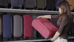 A mulher escolhe a mala de viagem na loja vídeos de arquivo