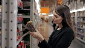 A mulher escolhe no café da loja para o trabalho, mulher de negócios no supermercado Imagens de Stock