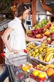A mulher escolhe o alimento no supermercado do mantimento Fotografia de Stock