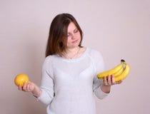 A mulher escolhe o fruto Fotos de Stock Royalty Free