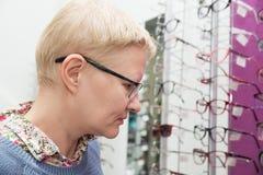 A mulher escolhe o quadro para vidros Foto de Stock Royalty Free