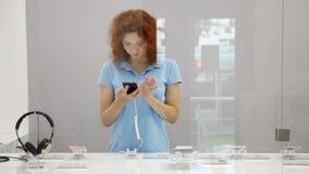 A mulher escolhe o smartphone em uma loja filme