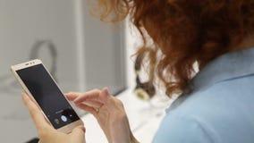 A mulher escolhe o smartphone em uma loja vídeos de arquivo