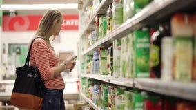 A mulher escolhe o suco no supermercado filme