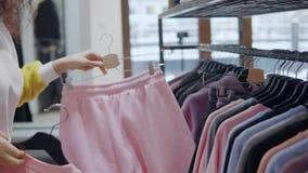 A mulher escolhe a roupa em uma alameda video estoque