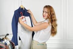 A mulher escolhe a roupa em uma loja de roupa Foto de Stock Royalty Free