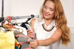 A mulher escolhe a roupa na loja Foto de Stock Royalty Free