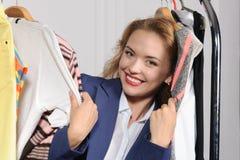 A mulher escolhe a roupa na loja de roupa Foto de Stock