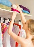 A mulher escolhe a roupa no armário do vestuário em casa Imagem de Stock Royalty Free