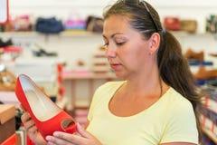 A mulher escolhe sapatas vermelhas em uma loja Imagem de Stock