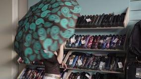 A mulher escolhe um guarda-chuva na loja filme