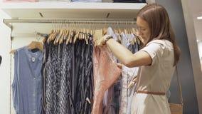 A mulher escolhe um vestido na loja filme