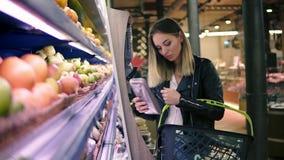 A mulher escolhe vegetais no supermercado Jovem mulher loura que escolhe produtos no shopping A menina está perto do video estoque