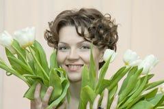 A mulher esconde atrás de um ramalhete dos tulips brancos Imagem de Stock