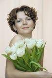 A mulher esconde atrás de um ramalhete dos tulips brancos Fotografia de Stock