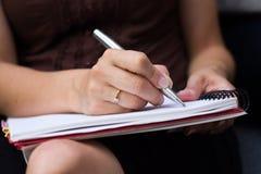 A mulher escreve em um papel Fotos de Stock Royalty Free