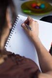 A mulher escreve em um papel Foto de Stock Royalty Free