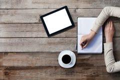 A mulher escreve em um papel com a tela da tabuleta digital ao lado dela Fotos de Stock Royalty Free