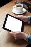 A mulher escreve em um papel com a tela da tabuleta digital ao lado dela Imagem de Stock
