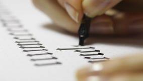 A mulher escreve a pena com letras caligráficas vídeos de arquivo
